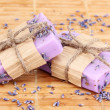 Hand-made lavender soaps on wooden mat - Stock Photo