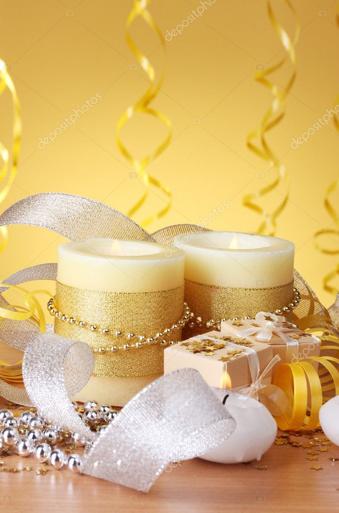 Beautiful candles, gifts and decor on wooden table on yellow background — Stock Photo #9517023