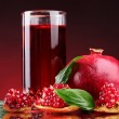 Ripe pomergranate and glass of juice on red background - Foto Stock