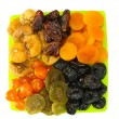 Delicious dried fruits on plate isolated on white - Stock Photo