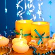 Beautiful candles, gifts and decor on wooden table on blue background — Stock Photo