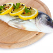 Fresh fish with lemon, parsley and pepper on wooden cutting board isolated on white - Foto Stock