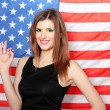 Beautiful young woman with the American flag on the background — Stock Photo #9535492