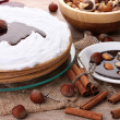 Cake on glass stand and nuts on wooden  table — Stock Photo