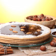 Cake on glass stand and nuts on wooden  table on yellow background - Stock Photo