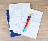 Math, physics and geometry on copybook page on a wooden table — 图库照片