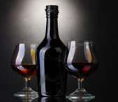 Copos de conhaque e garrafa em fundo cinza — Foto Stock