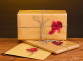 Parcels and envelope with sealing wax on wooden table on brown background — Stock Photo