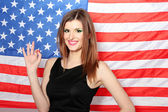 Beautiful young woman with the American flag on the background — Stock Photo