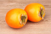 Two appetizing persimmons on wooden background — Stock Photo