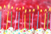 Beautiful birthday candles on red background — Stock Photo