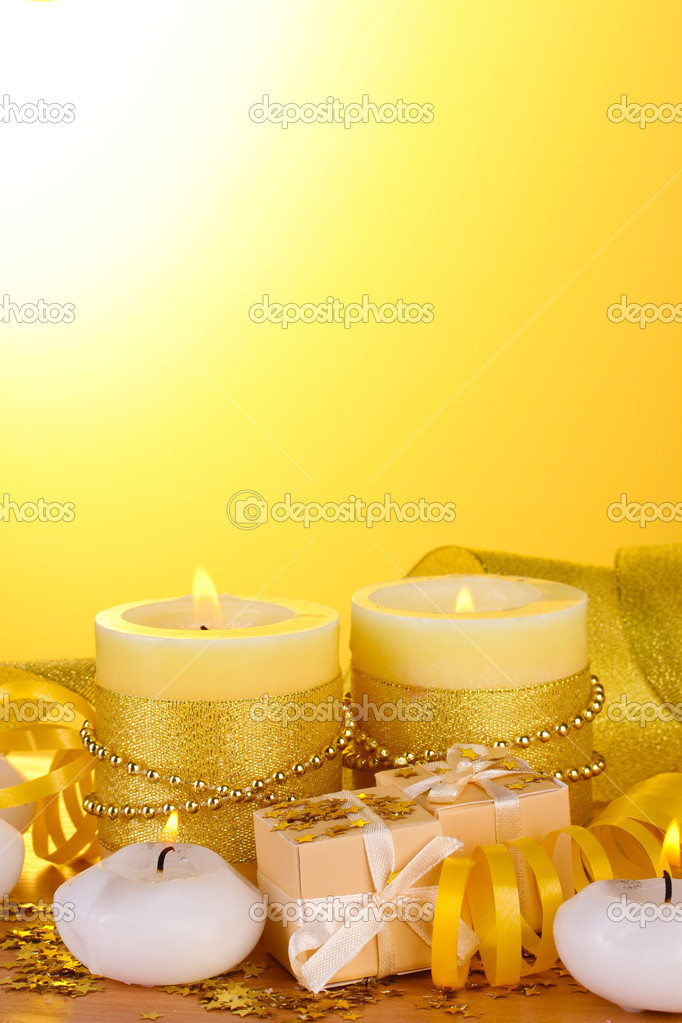 Beautiful candles, gifts and decor on wooden table on yellow background  Stock Photo #9534820