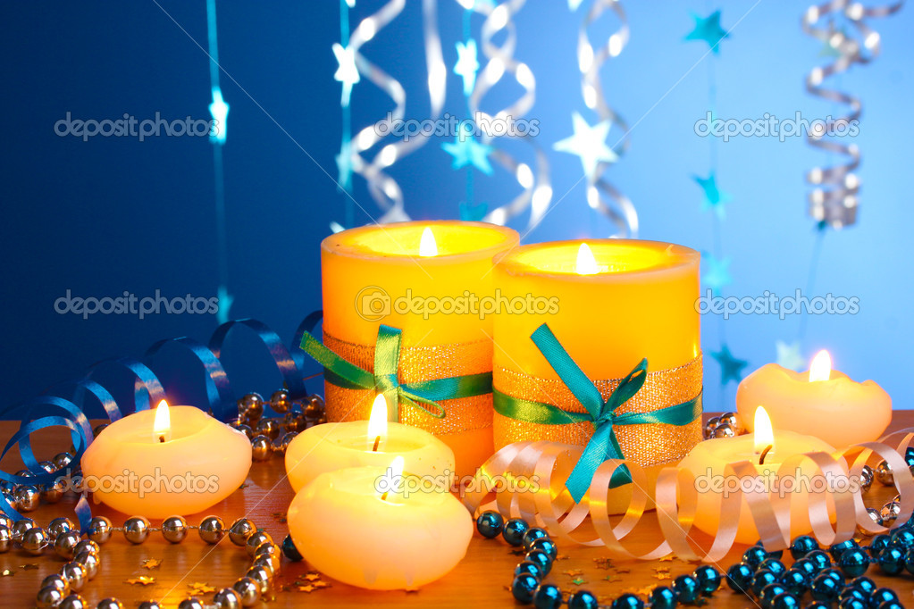 Beautiful candles, gifts and decor on wooden table on blue background  Stock Photo #9534831