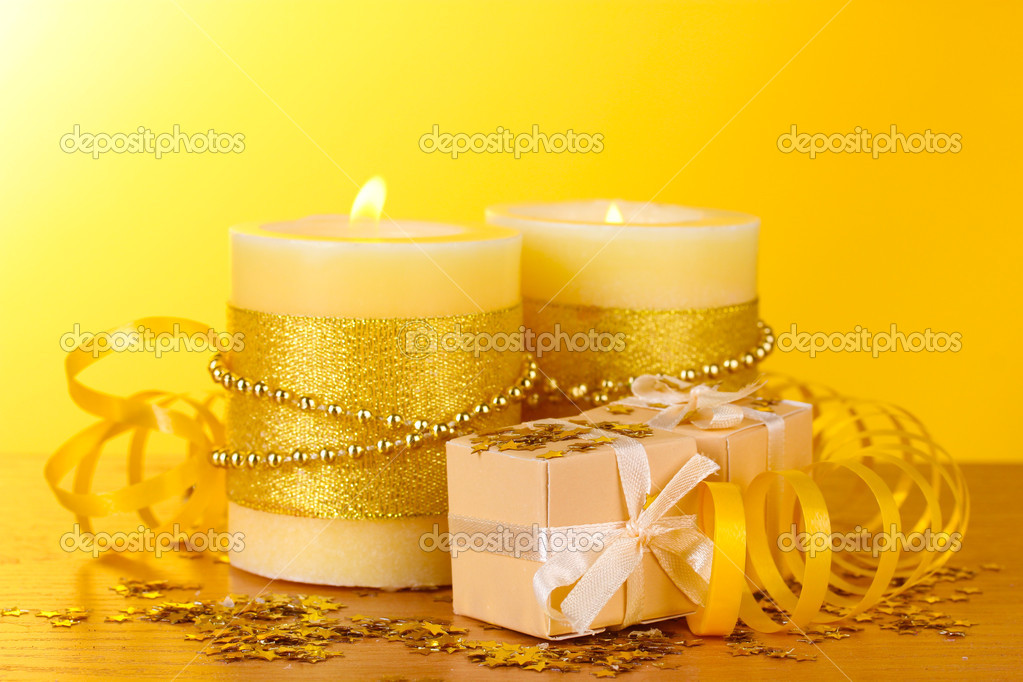 Beautiful candles and gifts on wooden table on yellow background  Stock Photo #9538252