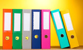 Bright office folders on wooden table on yellow background — Stock Photo