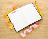 Planning of diet. Notebook measuring tapes and pen on wooden table — Stockfoto