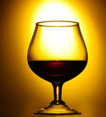 Glass of cognac on yellow background — Stock Photo