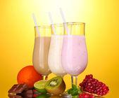 Melk schudt met vruchten en chocolade op gele achtergrond — Stockfoto