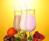 Milk shakes with fruits and chocolate on yellow background — Stock Photo