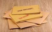Enveloppen met top geheime stempel op houten achtergrond — Stockfoto