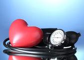 Black tonometer and heart on blue background — Stock Photo