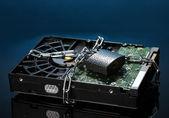 暗い青色の背景にあるチェーン上のハード ディスク ドライブ — ストック写真