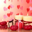 Beautiful candles with romantic decor on a wooden table on a red background — Stock Photo #9596654