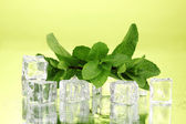 Fresh mint leaf and ice cubes with droplets on green background — Stock Photo