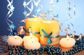 Beautiful candles, gifts and decor on wooden table on blue background — Fotografia Stock