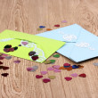 Color envelopes and confetti on wooden background — Stock Photo