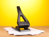 Black office hole punch with paper on yellow background — Stock Photo