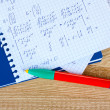 Math on copybook page on a wooden table - Stock Photo