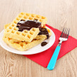 Tasty waffles with chocolate on plate on wooden background — Stock Photo