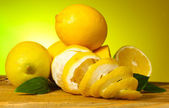 Ripe lemons with leaves on wooden table on green background — Stock Photo