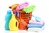 Clothes with detergent in orange plastic basket isolated on white — Stock Photo