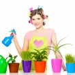 Beautiful happy young housewife sprays plants in flowerpots isolated on white - 图库照片