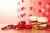 ロマンチックな装飾が施された木製のテーブル、赤の背景に美しいキャンドル — ストック写真