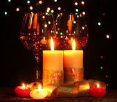 Beautiful candle and glasses of wine on wooden table on bright background — Stock Photo