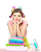 Beautiful young housewife with iron and pile of clothes isolated on white — Stock Photo