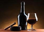Láhve a sklenky brandy a doutník na dřevěný stůl na hnědé pozadí — Stock fotografie