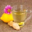 Healthy ginger tea with lemon and flower on sackcloth - Stock Photo