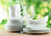 Clean dishes on wooden table on green background — ストック写真