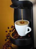 Kahve kupası kahverengi zemin üzerine dökülen espresso makinesi — Stok fotoğraf