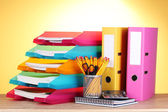 Bright paper trays and stationery on wooden table on yellow background — Stock Photo