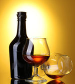 Glasses of brandy and bottle on yellow background — Stock Photo