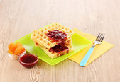 Tasty waffles with jam on plate on wooden background — Stock Photo