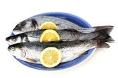Fresh fishes with lemon on plate isolated on white — Stock Photo