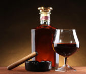 Bottle and glass of brandy and cigar on wooden table on brown background — Stock Photo