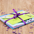 Bunch of color envelopes with ribbon and confetti on wooden background — Stock Photo #9694251