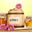 Sweet honey in barrel and jars with drizzler on wooden table on green background — Stock Photo